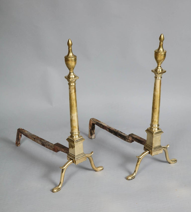 Fine pair of 18th century neoclassical brass andirons having urn finials over doric column shafts, standing on square plinth bases having cabriole legs with spurs over shoe feet.  Possibly Philadelphia, circa 1780.