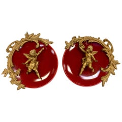Pair of Neoclassical Bronze Putti on Red Porcelain Plates Plaques Wall Decor