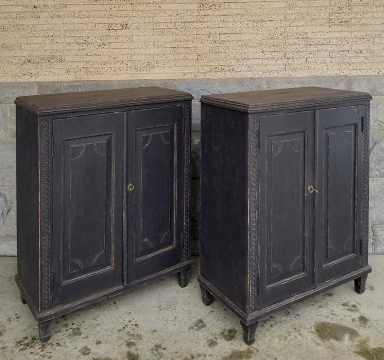 Pair of Swedish half-height cabinets, circa 1840 and perfect for use as sideboards. Each has a pair of raised panel doors with incised detail, guilloche carvings at the sides and beading around the tops. Inside are two fixed shelves. Tapering,