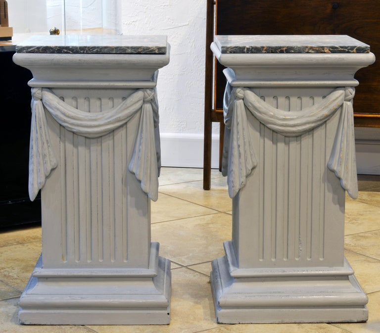 This pair of neoclassical Gustavian style carved and gray painted pedestals are equally useful as lamp tables or end tables. They feature antique marble tops above molded cornices, fluted sides decorated by swags continuing all around and rest on