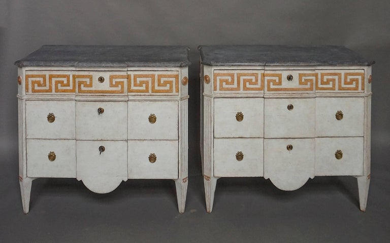 Pair of Swedish commodes, circa 1880, with paneled facade, the top drawers having raised Greek key molding. Shaped top and canted corners with rondels above reeded corner posts and tapered legs. The boldly curved aprons on the bottom drawers add to