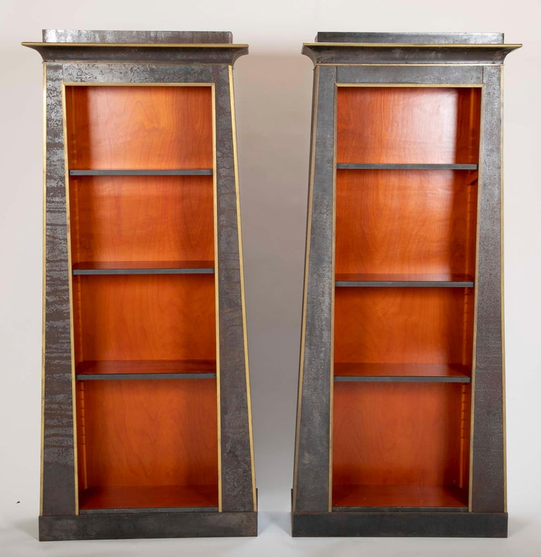 Stunning pair of unique custom made industrial neoclassical style bookshelves with iron over wood and brass trim. Each in the form of an ancient Egyptian doorway making for a very modern interpretation of the antique. With five adjustable shelves