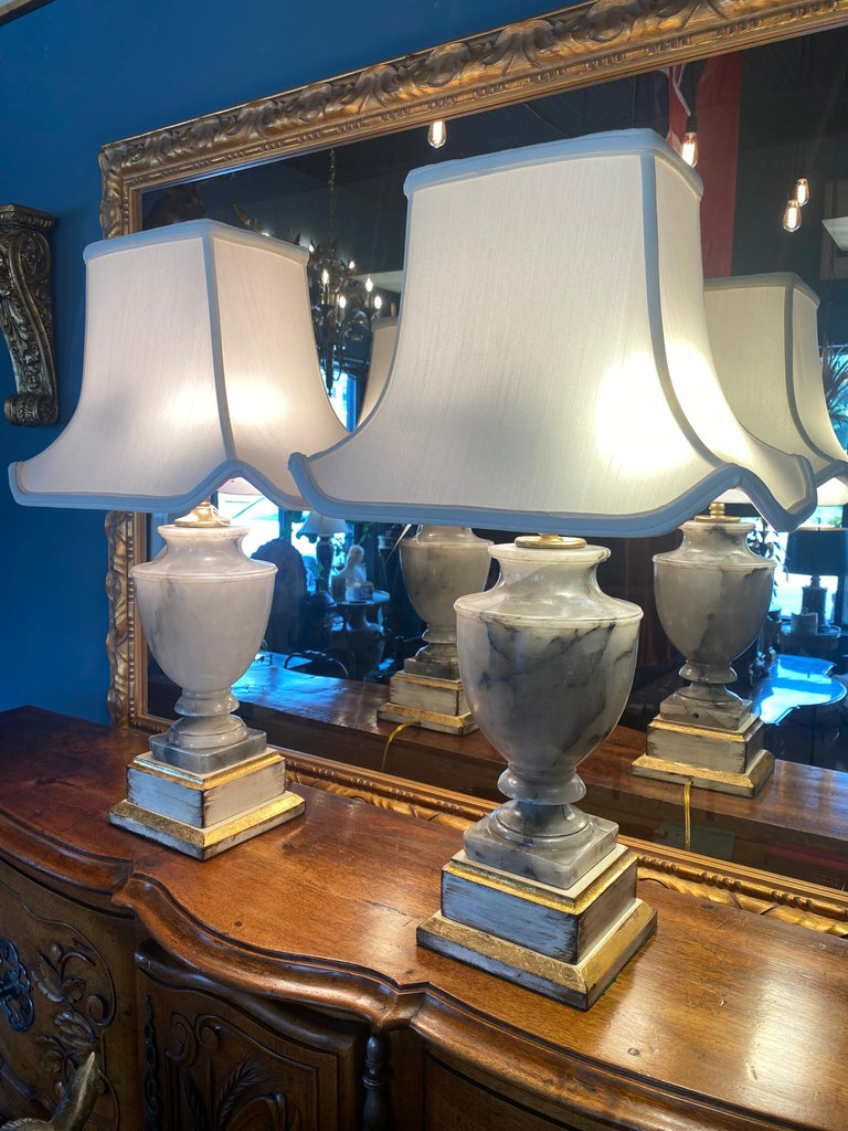 A pair of carved Oynx Urn form lamps mounted on lacquer and gilded Mahogany bases, new wiring. Pagoda lamp shades. Two horizontal sockets with pull cords in each lamp. Brass posts and finials. Bases are lined with felt on the bottoms.   Measures: