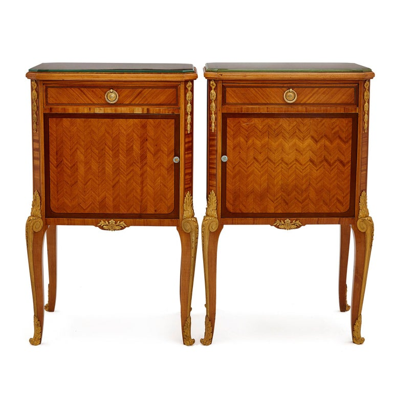 Pair of neoclassical style bedside cabinets retailed by Au Gros Chêne French, late 19th century Dimensions: Height 83cm, width 50cm, depth 35cm  Designed in the refined Neoclassical style, this pair of bedside cabinets are crafted from hardwood