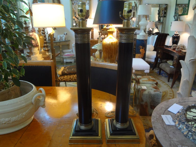 Large pair of neoclassical style tole column lamps with beautifully chased bronze detail. These stylish lamps would work well in a variety of interiors.