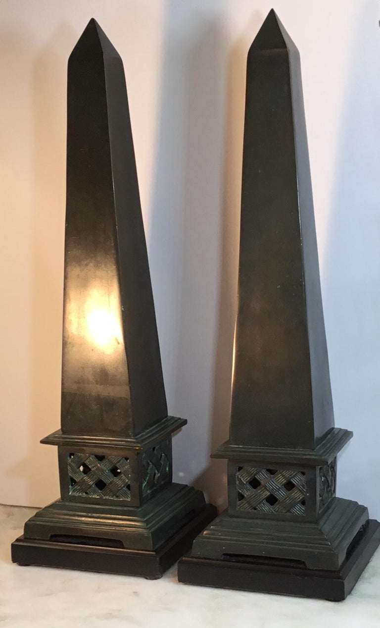 Elegant pair of obelisk made of solid bronze in dark green color, mounted on a black color brass base, beautiful object of art for display.
