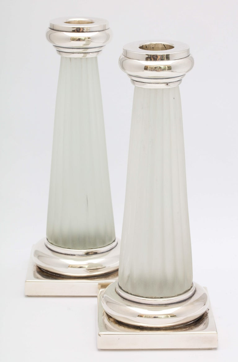Pair of neoclassical style, sterling silver-mounted frosted glass candlesticks, Italy, circa 1950s. Each candlestick measures 8 1/2 inches high x 3 1/4 inches wide (across base) x 3 1/3 inches deep (across base). Not weighted. Timeless design. Dark