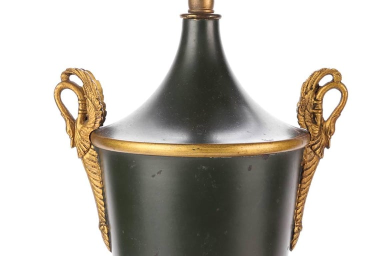 Pair of neoclassical tole urn form lamps, twin-light dark green tole urns with twin brass swan form handles and gilt palmette decoration, raised on tiered pedestal bases with gilt palmettes, adjustable top bars for shades.  Condition: Expected