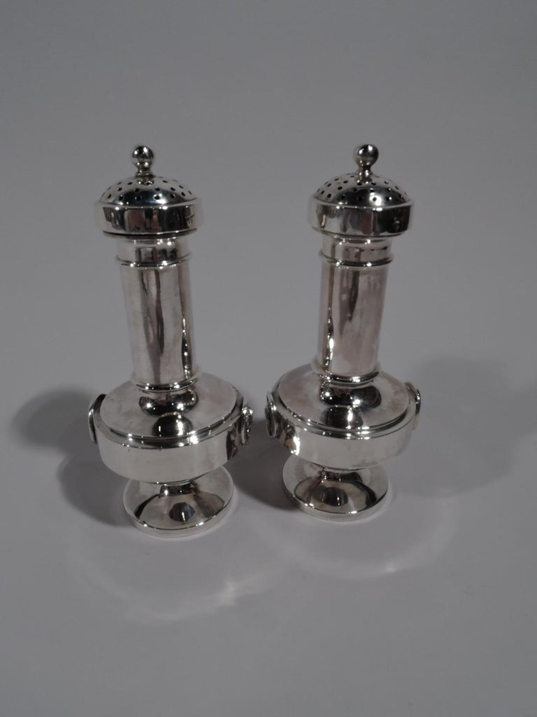 Pair of sterling silver Medallion salt and pepper shakers, circa 1870. Each: Cylindrical neck, bellied bowl, and round foot. Cover domed and overhanging with dense piercing. Two rondels with raised Classical head in profile on lined ground, one is a
