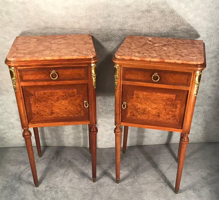 Pair of nightstands in the early Art Nouveau style from France. The very decorative nightstands date back to around 1890-1900. They are embellished with maple and mahogany veneer. The design still shows some influence from the earlier Napoleon III