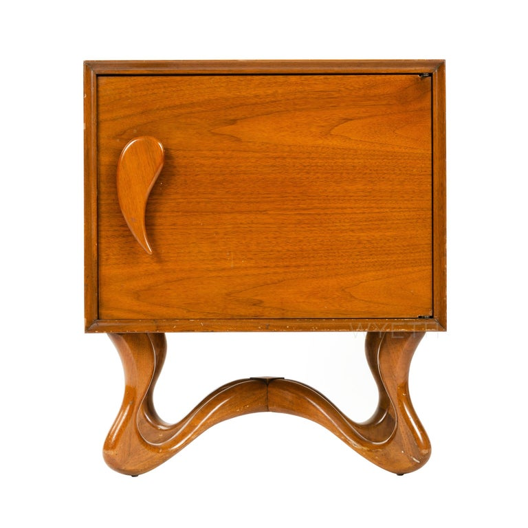 A pair of nightstands with hand carved teardrop handles and playful ribbon feet.