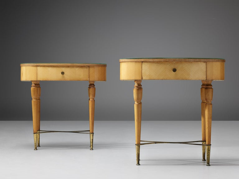 Pair of nightstands, beech, brass, glass, Italy, 1940s  These two nightstands show pure elegance. On brass feet the refined shaped legs evolve to the oval top with one drawer. The glass tabletop is colored green, the bright wood in combination
