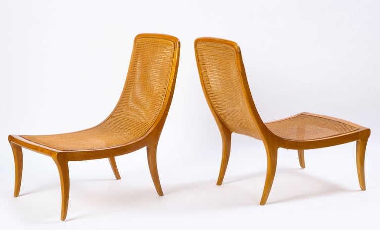 Pair of North European caned birch chaises or slipper chairs, mid-20th century. The armless chairs sit low to the ground and the caned seats are constructed in a dramatic curving form. Clean, well-maintained in appearance, and structurally sound,