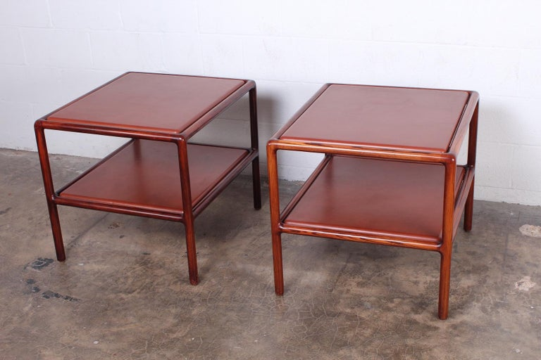 A pair of oak framed tables with inset leather tops by Ward Bennett.
