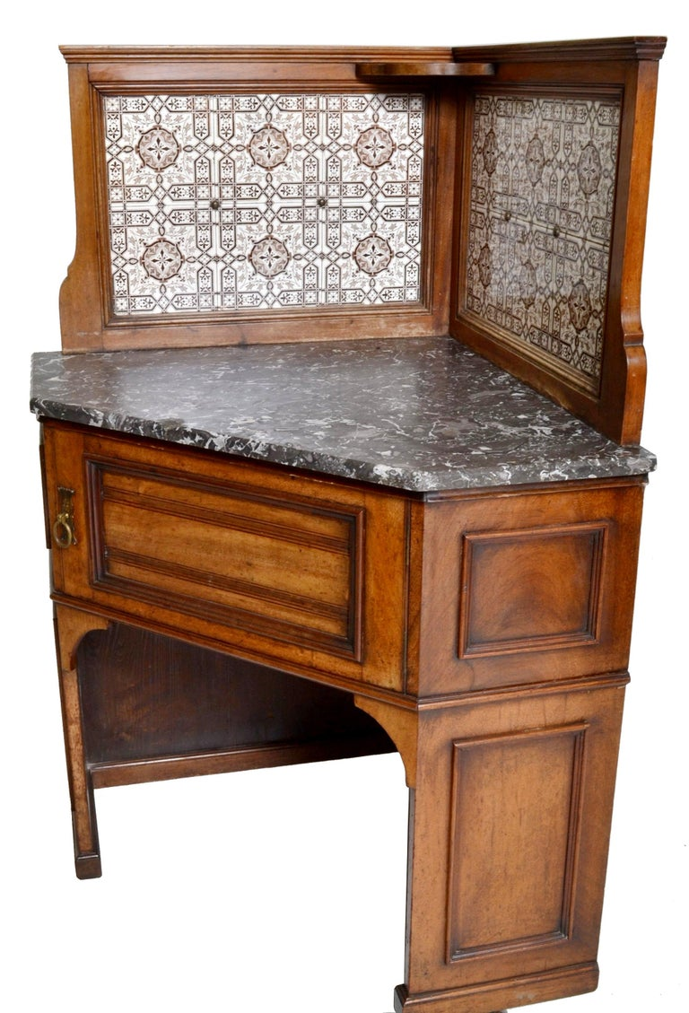 19th century pair of oak corner washstands by Maple of London, in the Aesthetic Movement taste, with Minton's tiles, circa 1875. The galleried splashbacks inlaid with Minton's tiles, each washstand having a variegated marble top. Each having the