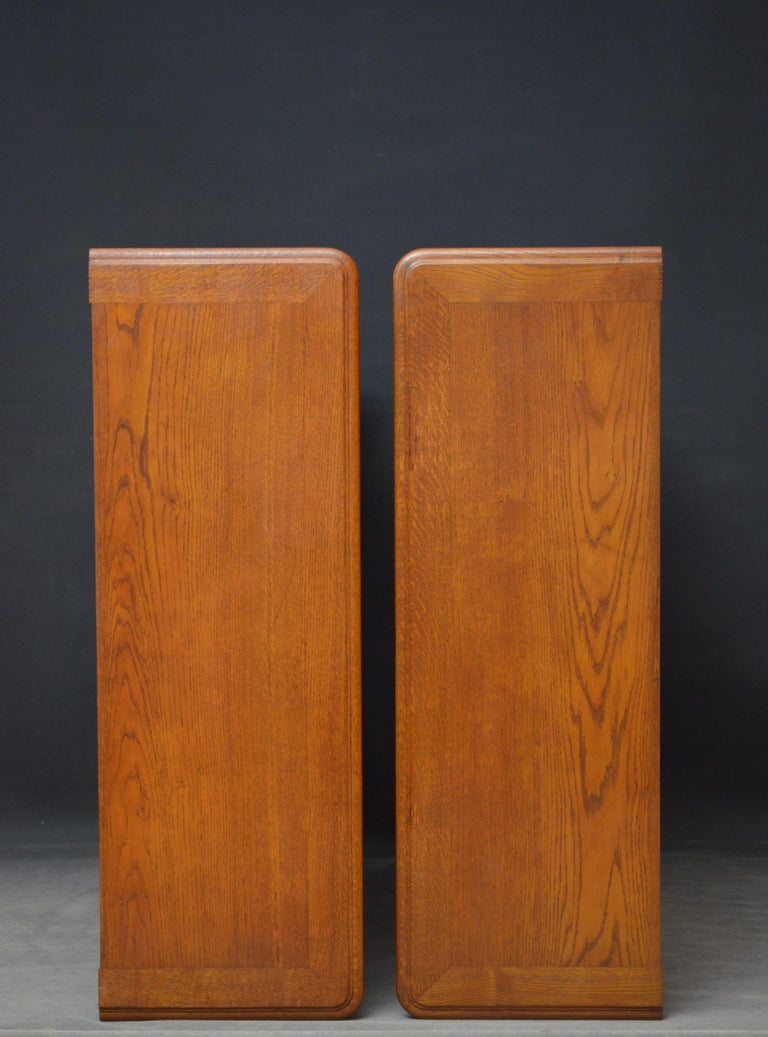 K0442 pair of turn of the century solid oak open bookcases, each bookcase having solid top above 2 height adjustable shelves flanked by rounded corners and fielded paneled sides, standing all standing on plinth base. This pair of antique bookcases