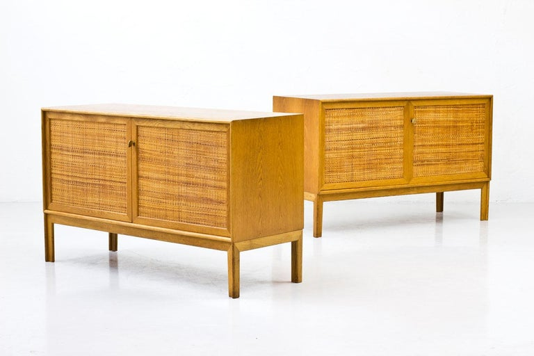 Pair of sideboards designed by Alf Svensson for Bjästa Möbelfabrik in Sweden during the 1960s.  Made from oak with two doors panel covered by rattan webbing. Brass key.  Inside in birch with adjustable shelves. Stamped by maker.  Length of each