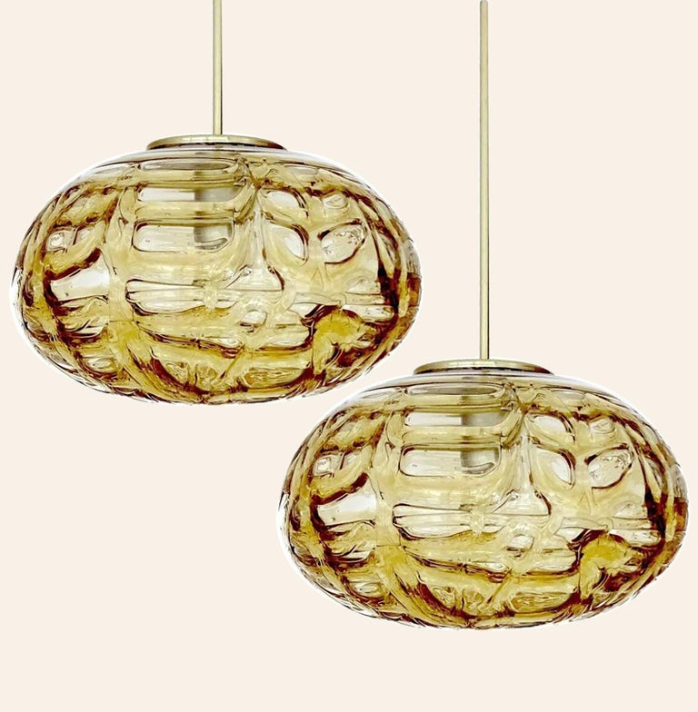 Doria ceiling light with an oval Murano amber glass and brass glass ball. Heavy quality, gives a wonderful light effect when it is on. Amber glass, brass. Period: 1970 Dimensions: H 7.5