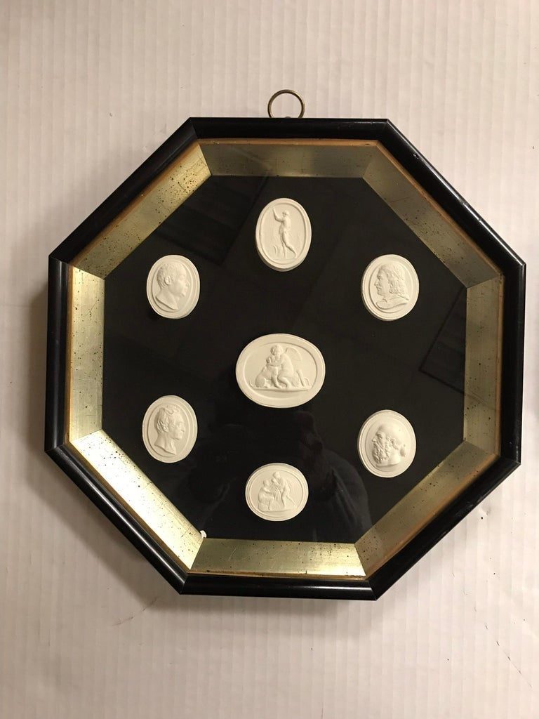 Framed, Greco-Roman plaster intaglios mounted on black velvet. Victorian black and gold octagonal frame protected in shadowbox. Each shadowbox contains 7 intaglios.
