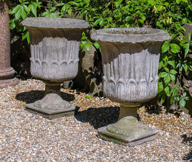 A pair of octagonal mid-20th century reconstituted stone urns in the neoclassical style with carved foliate detail raised on small socles, English, mid-20th century.