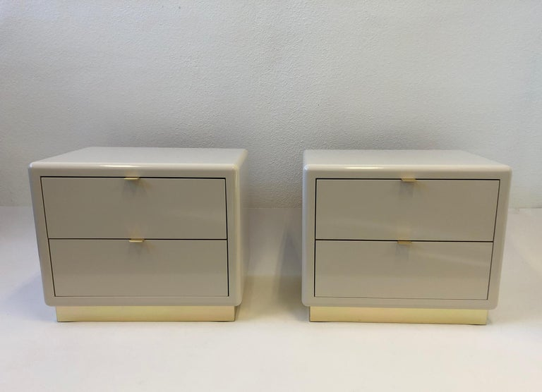 A glamorous 1980s pair of two drawer nightstands by Steve Chase. The nightstands are constructed of wood that's off white polished lacquered, the pulls and the base are brass. 