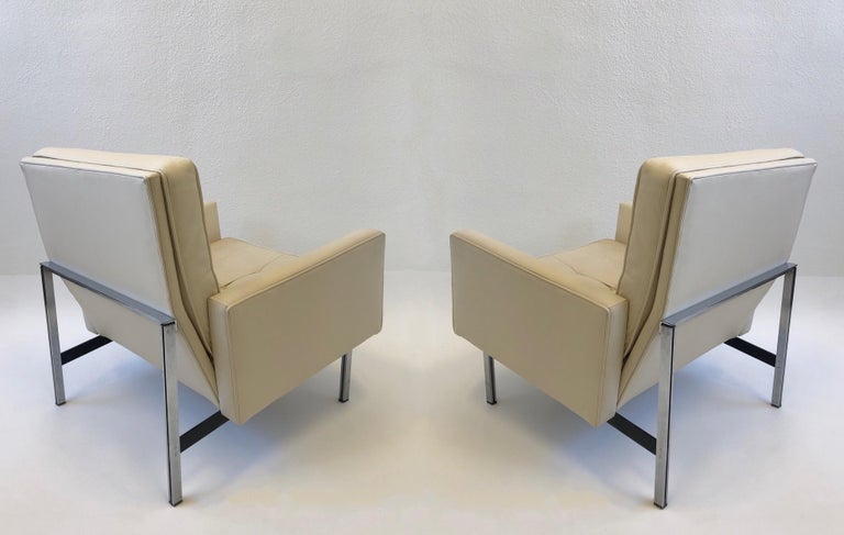 """Beautiful 1950's off white leather with parallel bar stainless steel legs lounge chairs designed by Florence Knoll for Knoll. This came out of the embassy of Australia. The sofa is also available. Measurements: 30"""" wide, 30"""" deep, 31"""" high, 21.5"""""""