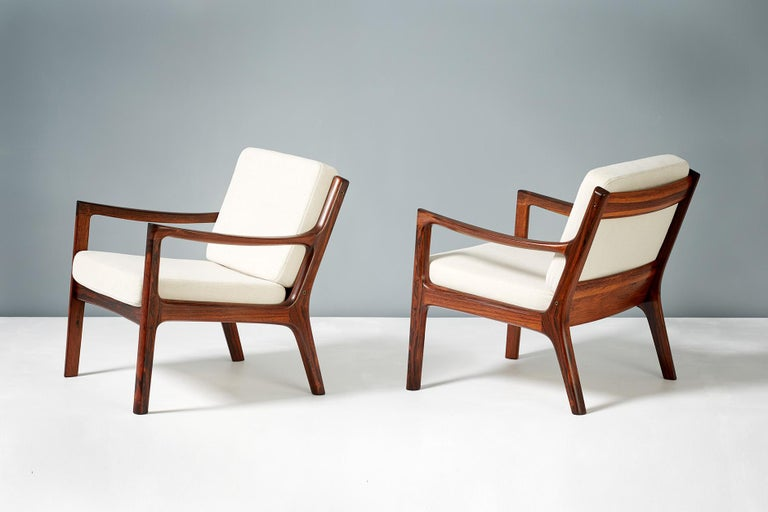 Limited edition pair of this iconic design in highly figured Brazilian rosewood rosewood, produced by France & Son in Denmark, circa 1960. Includes maker's badge under seat. The new cushions have been recovered in pale cotton/linen fabric.