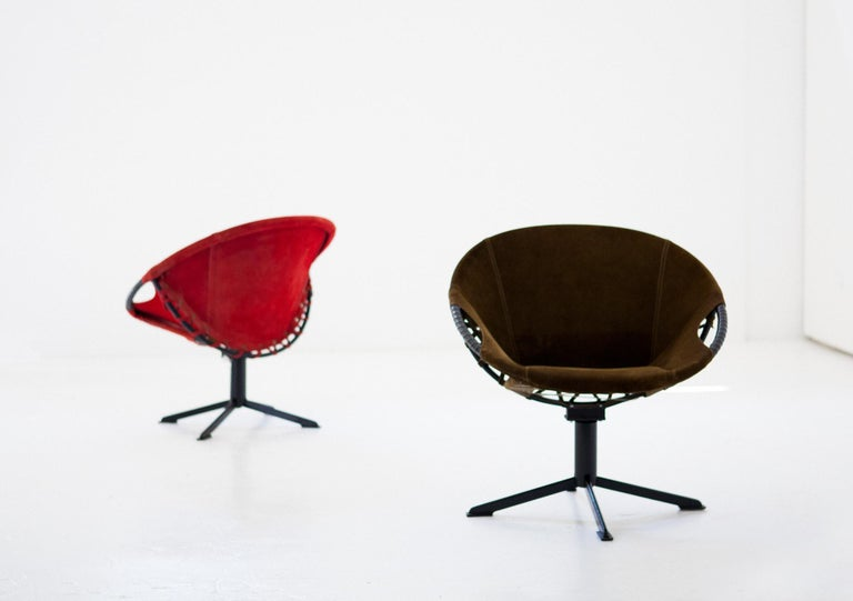 Pair of Mid-Century Modern armchairs, manufactured in 1960s.  These two easy chairs are swivel, with an iron frame and the seat in natural suede leather, one is red and one olive green. The frame of the chair has new black enamel, the leather has