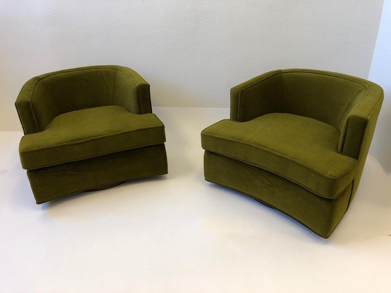 A spectacular pair of swivel lounge chairs designed by Harvey Probber in the 1950s. The chairs have been newly recovered in a beautiful olive green mohair fabric. The base is dark brown stained oakwood. One of the chairs retains the Probber label