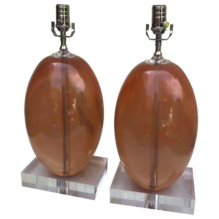 Pair of heavy orange ellipse-shaped resin table lamps on thick Lucite base.