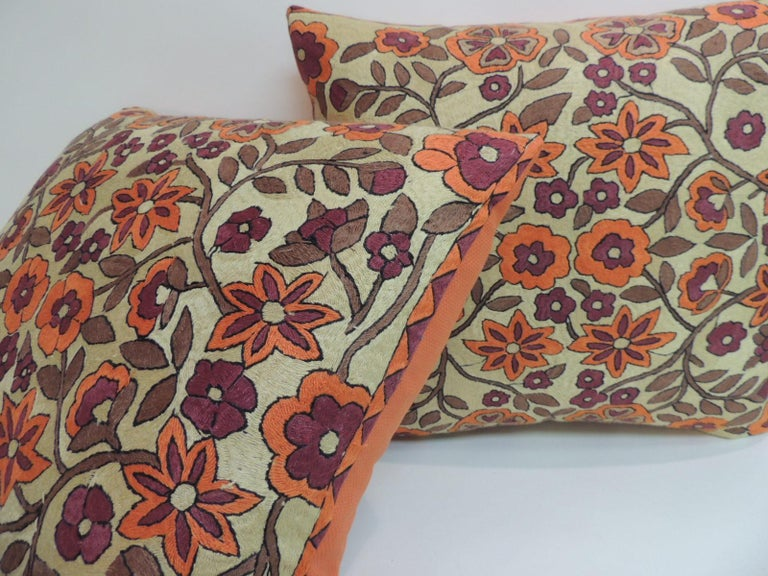 Pair of orange floral pattern Suzani vintage decorative pillows. Handcrafted with a basket weave orange linen backings. Textile from Central Asia. In shades of soft orange, purple, bright orange, brown and yellow. Suzani decorative pillow