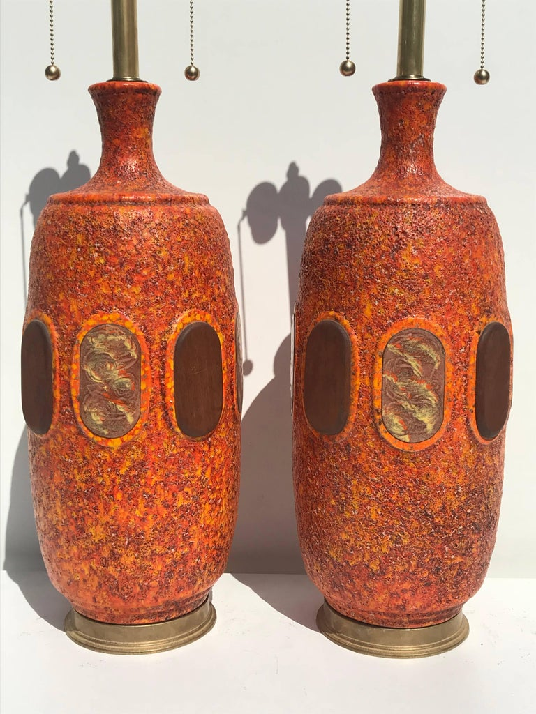 Pair of orange lava glazed ceramic lamps in the style of Marbro. Total height with shade is 44