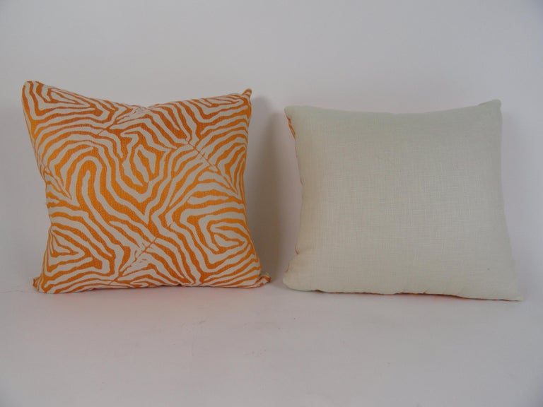 Pair of orange and beige zebra print pillows with beige cotton backing. 80/20 down filled. 24