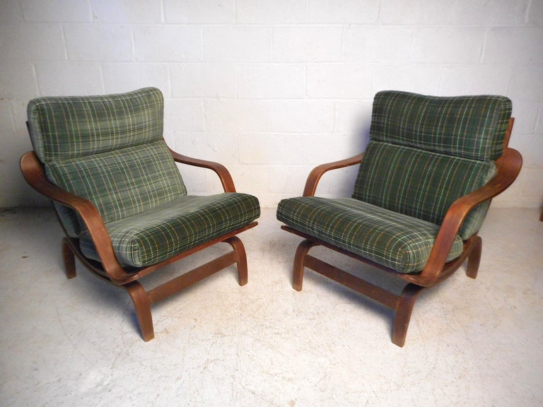 This stylish pair of midcentury lounge chairs feature a molded wood frame, contoured armrests, and comfortable seat cushions covered in a green plaid upholstery. Please confirm item location with dealer (NJ or NY).