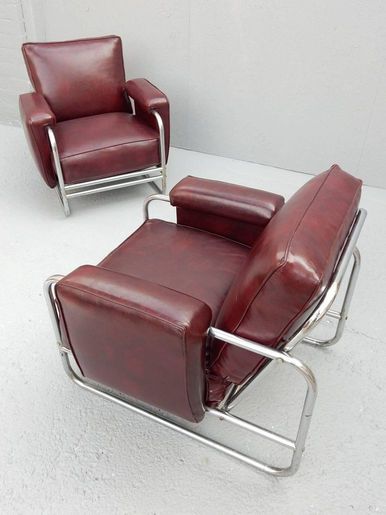 Pair of lounge chairs of chrome-plated steel tubing with seat, arm and back cushions covered in thick cordovan Naugahyde.
