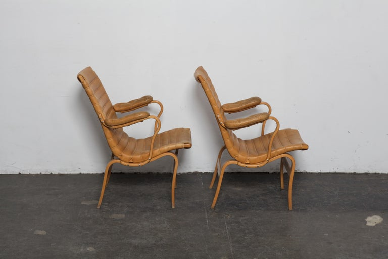 Pair of Bruno Mathsson 'Eva' chairs in beech and original horizontal tufted tan leather, Sweden, 1960s, produced by Dux. Leather and chair frames are in original, untouched condition but both show patina and wear.
