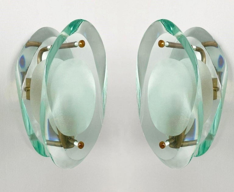 Pair of light sconces by Max Ingrand for Fontana Arte, Model 2093, Italy, 1960-1961. Organically shaped double lens cut panels of thick Murano profiled polished Murano glass with etched glass centers, polished brass mounted. The Model 2093 is one of