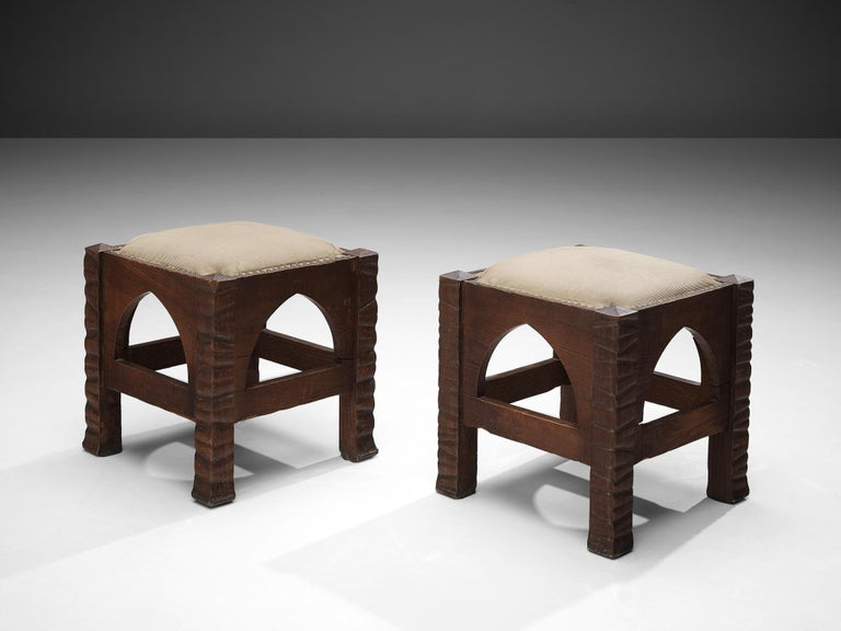 Ernesto Valabrega, pair of ottomans, oak, brass, fabric, Italy, ca. 1935  Ernesto Valabrega designed a rather particular ottoman. In between the legs one pointed arch each decorates the design. The legs are structured by a relief of unsymmetric