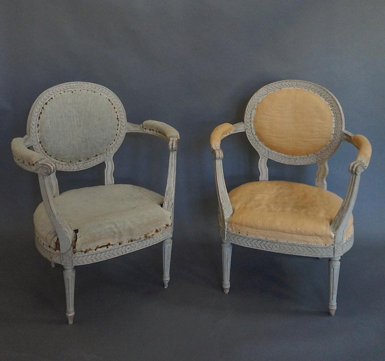 Pair of Gustavian style armchairs, Sweden, circa 1900, with oval backs and flared arms. Chain molding around the oval back and seat. Tapering round legs. Very comfortable.
