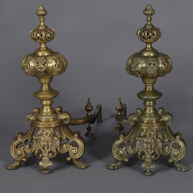 Pair of oversized Baroque style brass chenets feature graduated and pierced graduated bowls and finial over scroll and foliate base having central mask, circa 1890.