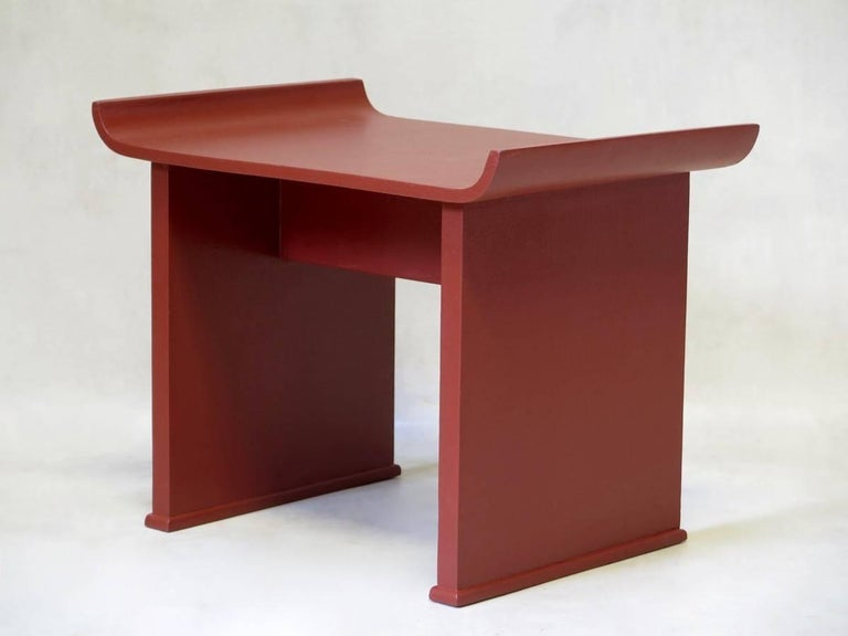Minimalistic pair of red-painted wooden side tables, the tops turning upwards at the edges, giving them an Oriental air.