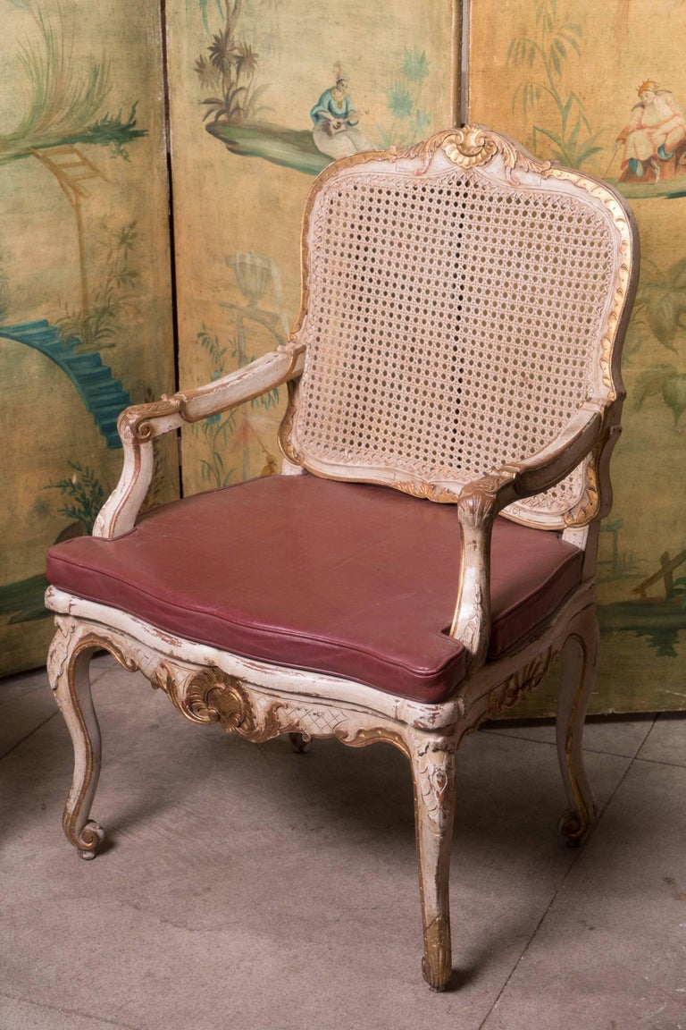 Pair of painted and gilded armchairs with leather seats.