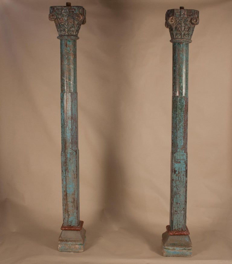 Beautiful pair of authentic teak wood columns from India, circa 1900. Colorful, yet subdued, the pillars have their original paint, a medley of blue and green, with hints of deep red. The Corinthian capitals are hand-carved with a floral design, and