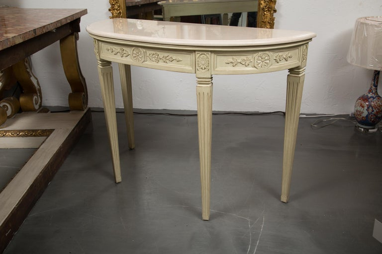 These are a Classic Italian hand carved and painted console tables. Each has a cream marble top over a carved frieze containing a central drawer. Both consoles are supported by square tapered fluted legs. Priced as a single item.
