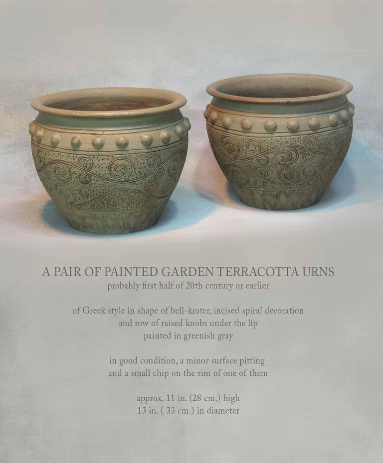 A pair of painted terracotta urns, probably first half of the 20th century or earlier, of a Greek style in shape of bell-krater, incised spiral decoration and a row of raised knobs under the lip, painted in a greenish grey. In good condition, a