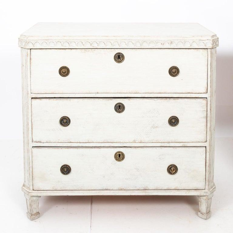 Pair of white painted Gustavian chest of drawers with metal hardware and historic paint that features original patina, circa 1880s. Please note of wear consistent with age including minor paint loss.