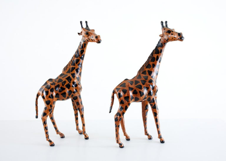 Charming pair of hand painted leather giraffe sculptures featuring a geometric pattern body and life like heads. Beautifully hand-crafted with expressive faces.