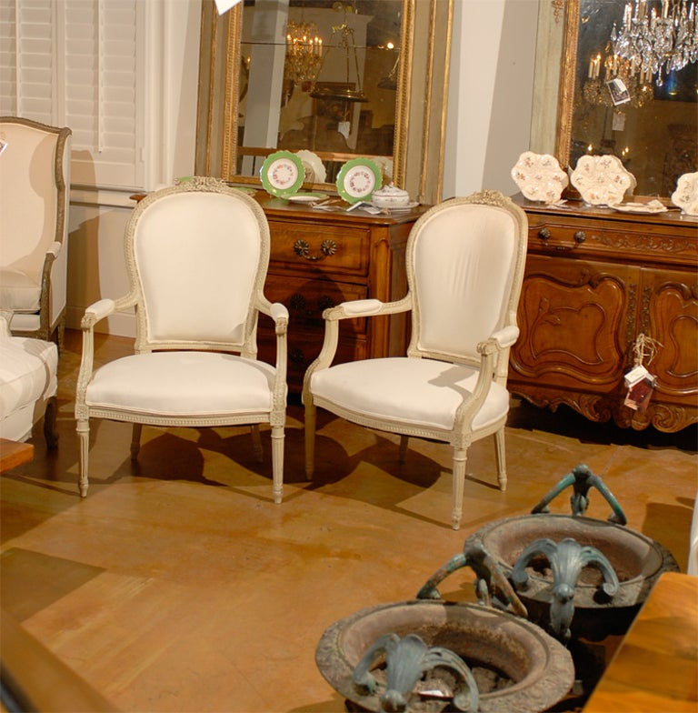 A pair of French Louis XVI style painted wood armchairs from the late 19th century, with carved motifs and new upholstery. Created in France during the 19th century, each of this pair of armchairs features a slightly curving back, adorned with a