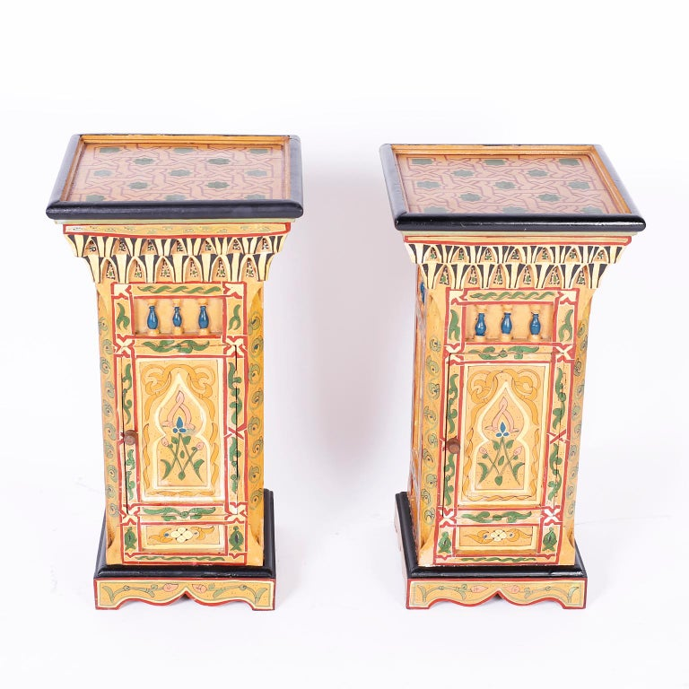 Pair of Moroccan wood stands carved, paneled and painted with geometric and floral designs in distinctive Mediterranean colors.