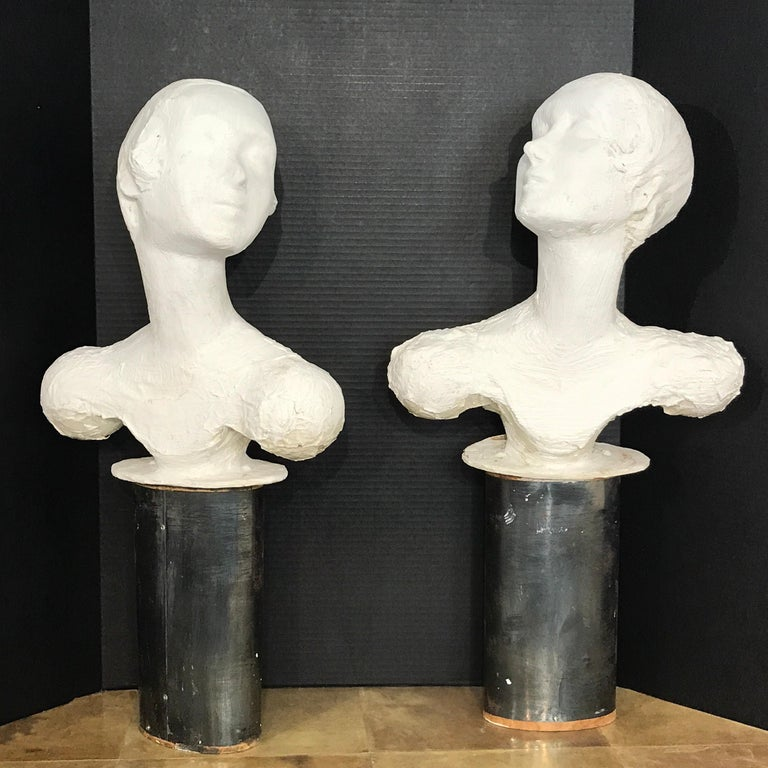 Pair of painted plaster flapper mannequin busts, realistically modeled and detailed, originally a display piece in a ladies' fashion store, or millinery or department store, each one with a oval weighted steel pedestal base. Probably fitted into the